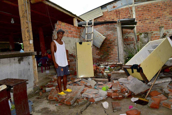 a-villager-is-standing-on-the-debris-of-his-collapsed-house