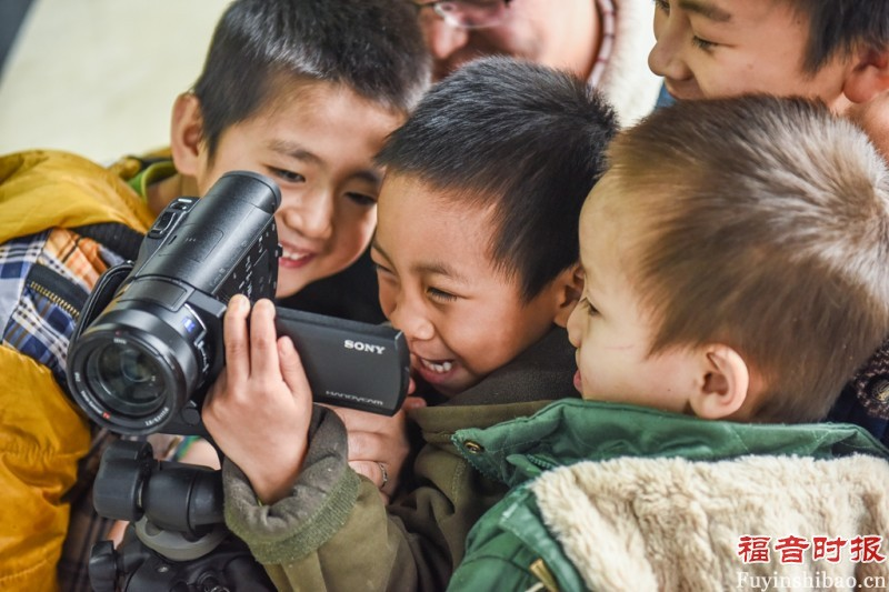 Close-up, Children of the Home of Hope are looking their videos by the CCD reporter.(credit: GospelTimes.cn)