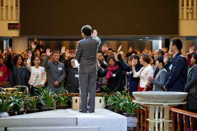 Commissioning Service in Haidian Church: The commissioned believers for new campuses are praying, led by Rev. Wu Weiqing. (credit: Haidian Church)