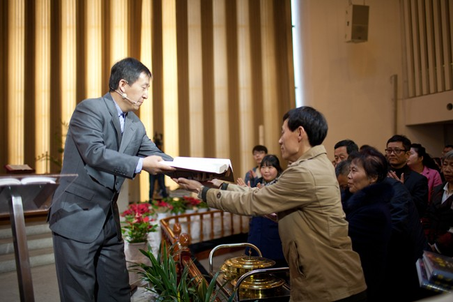 Commissioning Service in Haidian Church: Rev. Wu presided the service and sent handwritten versions of the Bible and hymnals as gifts to commissioned staff.(Credti:Haidian Church)