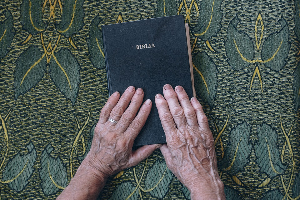 an-elderly-person-places-his-hands-on-the-bible