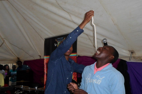 A South Africa pastor puts a white snake into the mouth of a believer (credit:anticult.kaiwind.com)
