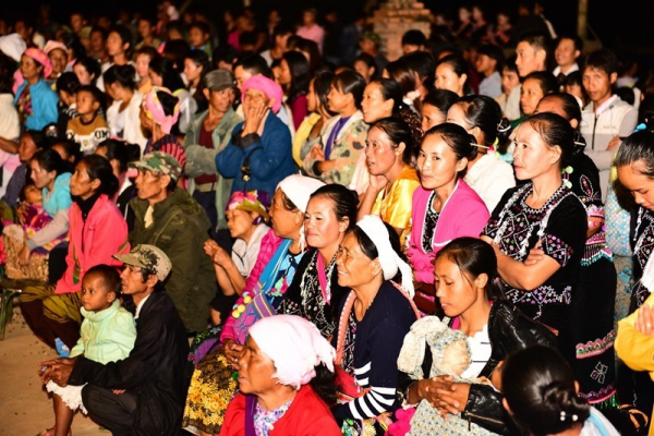 Believers watching the dancing, seated in the church yard.