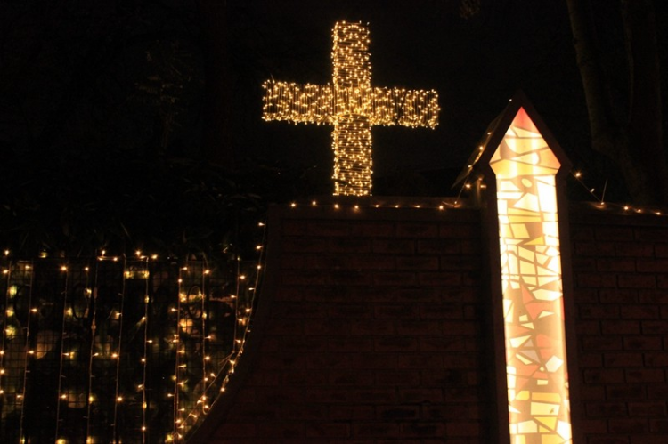 A cross stands outside of a church fence.