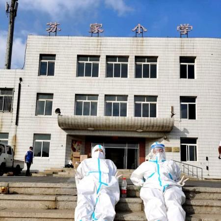 Ju Wanzhen and her sister lied on a concrete staircase to ease the tired body by the sunlight, in July 2020, due to the new cluster outbreak in China's coastal city Dalian.