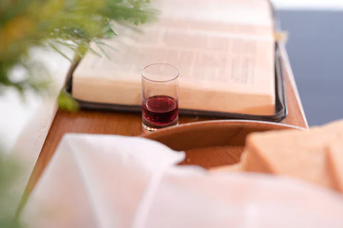 A cup of wine and bread are placed beside the Holy Bible.