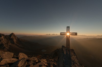 A cross on a hill facing the setting sun.