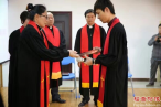 Pastor Feng Min (right) receives the Bible as the gift after the ordination.