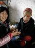 Sister Qiao serves an elderly leprosy survivor with joy.