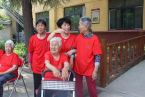 The elderly people and nurses wear uniform red T-shirts.