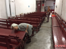 An elderly sister cleans the legs of the church pews.