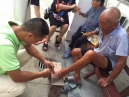 A Christian helped an elderly man cut his toenails.