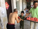 A boy gave a slice of watermelon to an elderly resident.