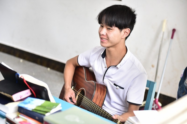A student plays a guitar to praise God.