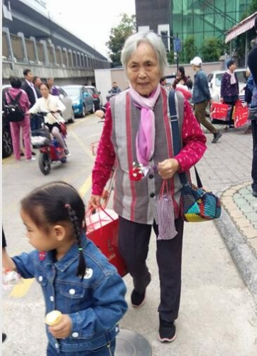An elderly woman receive a bonquet and a set of bedding from Hangzhou Chengbei Church, Oct. 14, 2018.