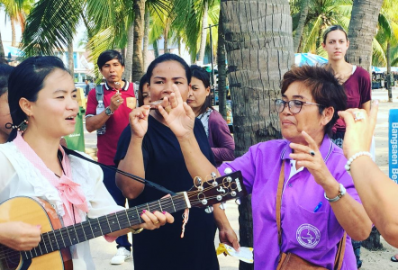 Pastor Fon of Zion MB Church, Khao Sam Muk, Thailand, plays guitar for the communion event on the beach.