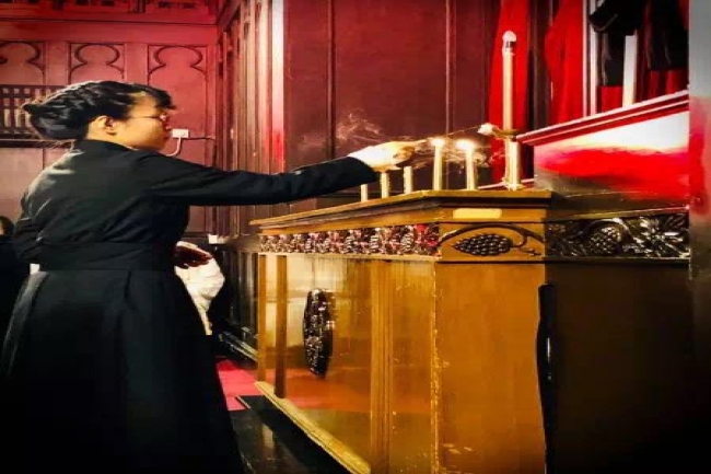 An acolyte extinguished one of the candles in the Tenebrae conducted in Shanghai Community Fellowship on Good Friday.