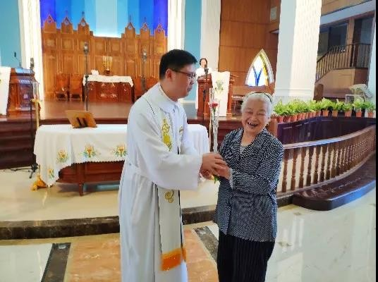 On May 12, 2019, a pastor gave a carnation to an old lady in Zhenli Church of Lianjiang, Fujian.