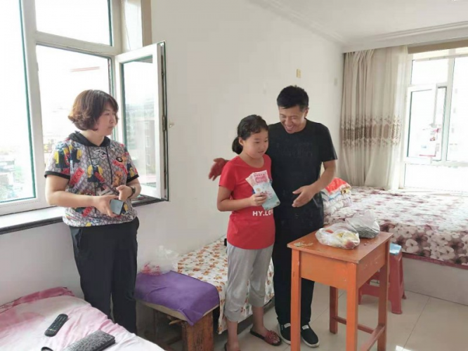 A worker of Nanzhan Church staff gave a grant to a poor girl on Aug 14, 2019.