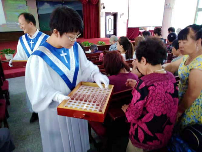 A pastor distributed the bread and cup to the congregation of Lühuajie Church, Anshan, Liaoning, on Sept 1, 2019.