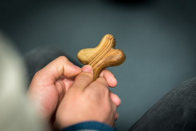 A man holds a cross in his hands.