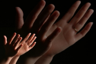 Big and small hands are raising up to worship God.